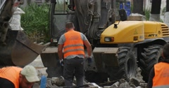 Workers in Orange Workwear Close Up Road Repair Yellow Excavator with Flasher - stock footage