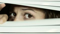 Brown-eyed girl looks through Venetian blinds disapprovingly and suspiciously Stock Footage