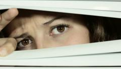 Suspicious young woman peeking though Venetian blinds nervously. Stock Footage