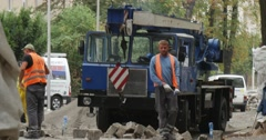 Workers in Orange Workwear Blue Truck Arrives Lorry With Hook Paving the Road Stock Footage