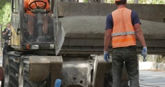 Workers in Orange Workwear Yellow Excavator Unloads the Granite Dust on the Stock Footage