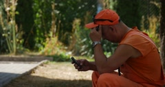 Worker Man in Orange Workwear And Cap is Sitting on the Piece of Concrete at Stock Footage