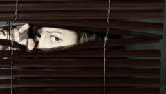 Girl peeps through Venetian blinds, looks to side suspiciously, eye brows raised Stock Footage