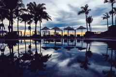 Stock Photo of Silhouette palm tree with umbrella and chair in the luxury hotel pool resort