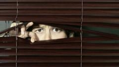 Young woman peeps through Venetian blinds and is startled Stock Footage