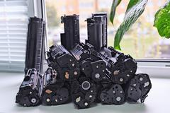 Cartridges from the printer stacked on the windowsill Office - stock photo
