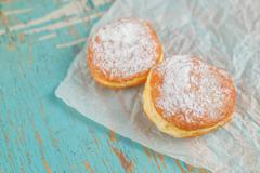Sweet sugary donuts on rustic table Stock Photos