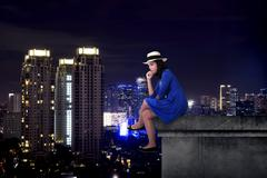 Asian tourist woman sitting on the building rooftop Stock Photos