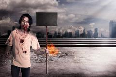 Male zombie holding wooden board over city on fire - stock photo