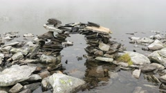 Odd sculpture of stones on the shore of a lake Stock Footage