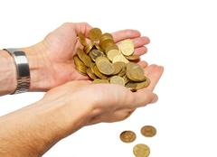 Many coins in cupped hands isolated on white. - stock photo