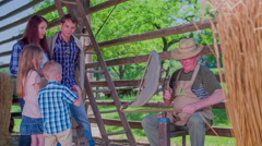 Family is looking on the old farmer during working Stock Footage