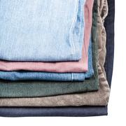 stack of different jeans and corduroys close up - stock photo