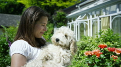 4K Beautiful woman holding cute pet dog in the garden Stock Footage