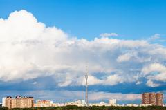 large cloud in blue sky over city with TV tower - stock photo