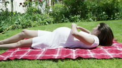 4K Beautiful pregnant woman sunbathing in the garden,  Stock Footage