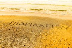 Stock Photo of Inspiration. Creative motivation concept written in the sand at the beach.