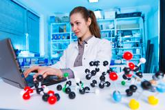Young woman scientist working at the laboratory. Model of molecule on a table Stock Photos