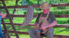 Old farmer with a hat is working on the historical tool Stock Footage
