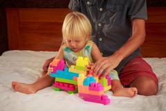 little blonde girl plays toy constructor with father on sofa - stock photo