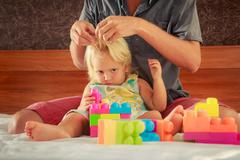 Little girl plays toy constructor father brushes her hair Stock Photos