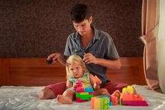girl plays toy constructor father brushes her hair - stock photo