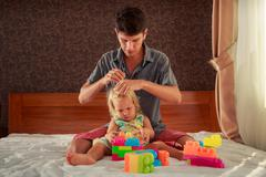 Girl plays toy constructor father brushes her hair Stock Photos