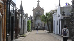 Woman with Backpack walks near Mausoleums in Reoleta Cemetery, Buenos Aires - stock footage