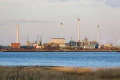 Wind turbines and industry in the harbor of Antwerp, Belgium with warm evenin Stock Photos