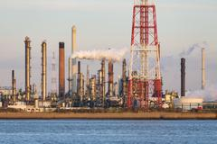 Stock Photo of A large oil refinery with flare stack in the port of Antwerp, Belgium with lo