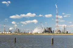 A refinery with tall flare stack in the port of Antwerp, Belgium with lots of - stock photo