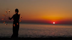 Girl manages fire near the sea at sunset Stock Footage