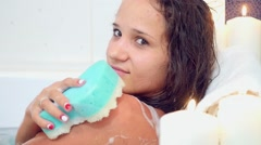 Beautiful young sexy brunette woman taking a relaxing bath with foam using Bath Stock Footage