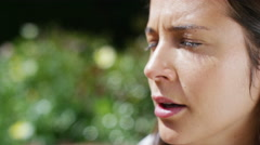 4K Woman with hay fever sneezes into a tissue as she sits in her garden Stock Footage