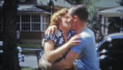 1953: Working class couples walking and kissing in residential area. - stock footage