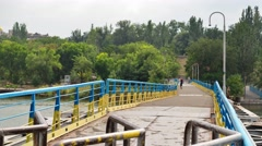 Pedestrian bridge over the river painted in colors of Ukrainian flag Stock Footage