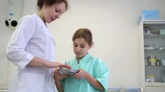 Girl and medical worker look at the content of metal bowl. Stock Footage