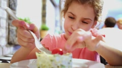 Little girl eats tomato with  salad sitting at table and plays same time. Stock Footage