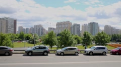 Cityscape with highrise buildings, blue sky and cars along road. Stock Footage