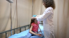 doctor in lab coat puts cap for encephalography on girl head - stock footage