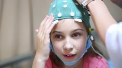 Stock Video Footage of hands inject electrically-conductive gel in cap on girl head.