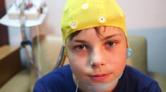 Boy in cap for electroencephalography sits near monitor Stock Footage