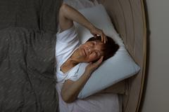 Top view of a senior woman staring at ceiling of bedroom during night time. I - stock photo