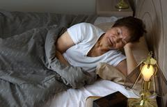 Senior woman restless at nighttime while trying to sleep - stock photo