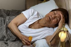 Senior woman preparing to take medicine at nighttime due to insomnia - stock photo