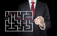 Businessman finding the solution of a maze Stock Photos