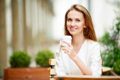 Woman drinking coffee at street cafe Stock Photos