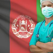 Surgeon with flag on background series - Afghanistan - stock photo