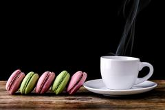 cup of coffee smoking with pink and green macaron on wood - stock photo