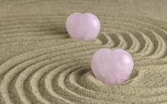 Rose Quartz heart in zen garden - stock photo